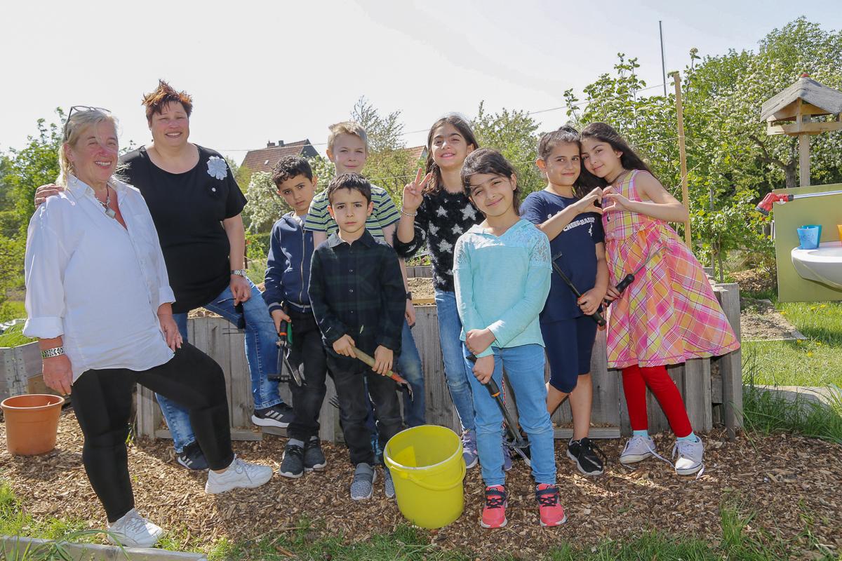 Marion Kirkham, Silke Kettling und die Grundschüler Leith, Tim, Mohammed, Shina, Daad, Hinous und Zahraa haben im Schulgarten des Kleingärtnerverein Rote Schanze die Gartensaison eröffnet.